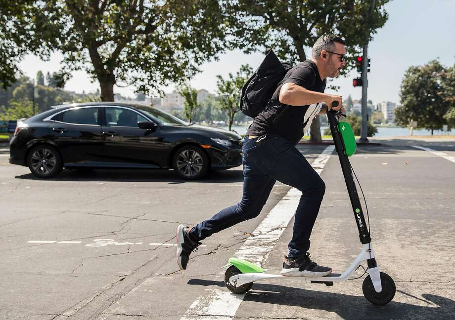 FILE - A man zips down Grand Avenue on a Lime electronic scooter near Lake Merritt in Oakland, Calif. Thursday, Aug. 16, 2018. A new self-driving e-scooter is coming as soon as next year. Photo: Jessica Christian, The Chronicle