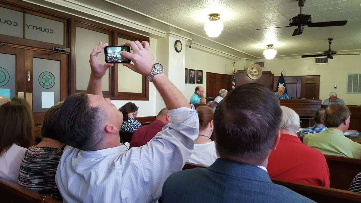 Spencer Walker holds up his cell phone to take a photo of the Liberty County Commissioners as they approve the new Veteran?'s Treatment Court during session on Tuesday, Aug. 28. The Iraqi Freedom combat veteran is a testimony of the court?'s success in his own life.