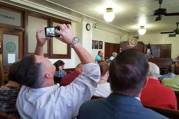 Spencer Walker holds up his cell phone to take a photo of the Liberty County Commissioners as they approve the new Veteran's Treatment Court during session on Tuesday, Aug. 28. The Iraqi Freedom combat veteran is a testimony of the court's success in his own life.