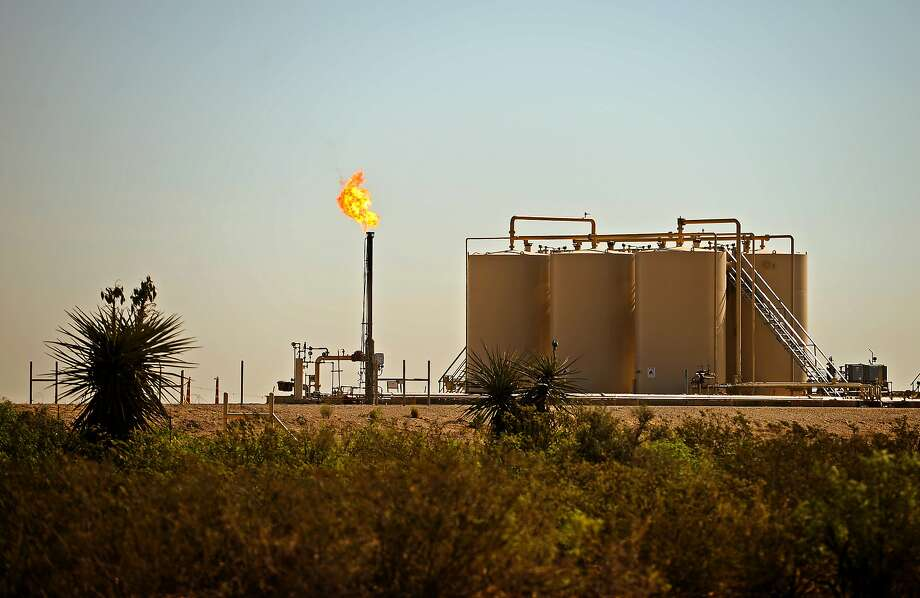 A natural gas flare is visible near storage tanks May 30, 2018, in Reeves County, Texas.  NEXT: See photos from the Permian Basin Oil Show over the years. Photo: James Durbin / For The Chronicle, For The Chronicle