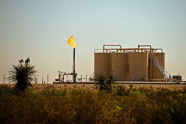 A natural gas flare is visible near storage tanks May 30, 2018, in Reeves County, Texas. CREDIT: TheOilfieldPhotographer.com