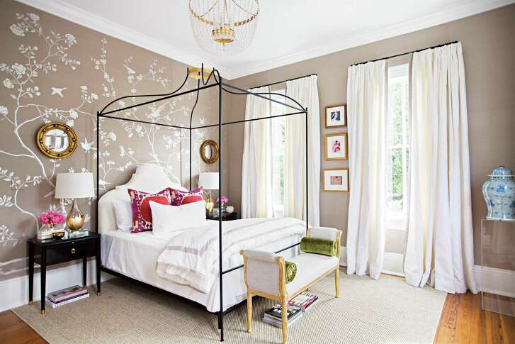 A wall of de Gournay wallpaper adds interest and a pair of small, convex mirrors help draw the eye up toward the bed's canopy.
