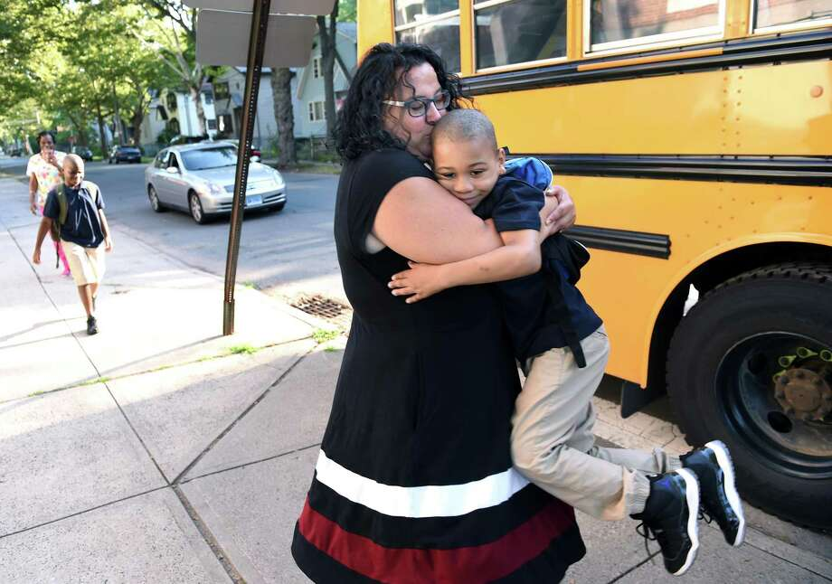 First grader Ahmir Woods jumped into the arms of leadership team member Lorrie Quirk as he arrives on the first day of school at Lincoln-Bassett Community School in New Haven Thursday. Photo: Arnold Gold / Hearst Connecticut Media / New Haven Register