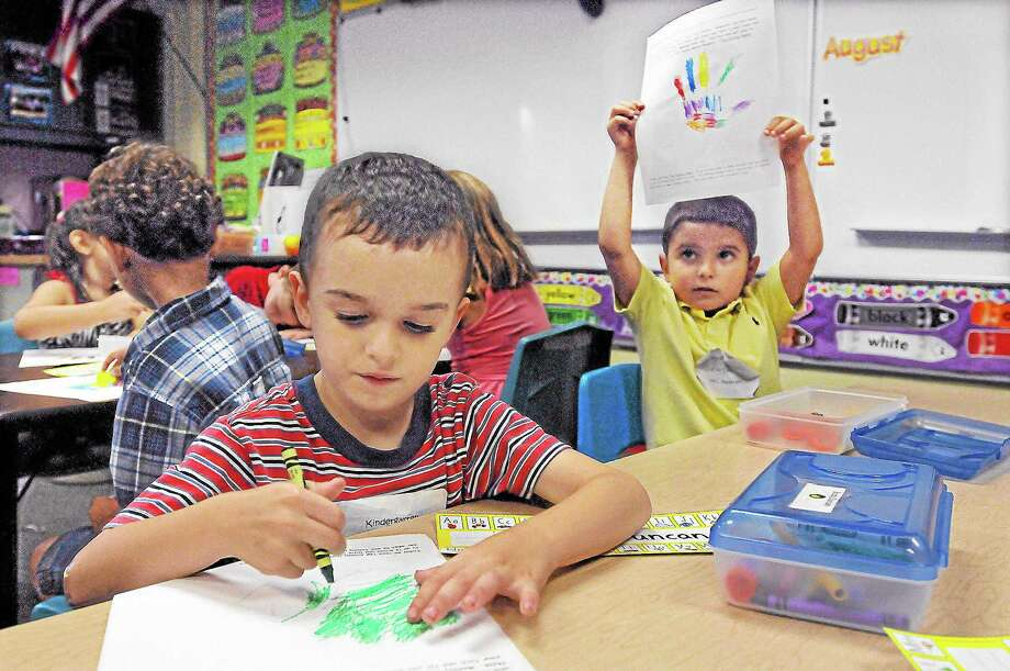 A Cromwell kindergartner raises his paper to show his teacher his completed work as a fellow student colors a picture of his hand at Edna C. Stevens Elementary School. Photo: File Photo / TheMiddletownPress
