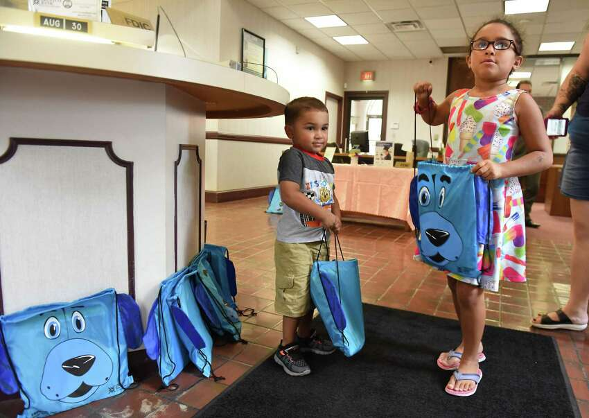 Tamren Turner, 3, of Troy and his sister Tatiana pick up their new backpacks at Trustco Bank on Thursday, Aug. 30, 2018 in Troy, N.Y. Trustco Bank was giving away backpacks with school supplies and free lunch. (Lori Van Buren/Times Union)
