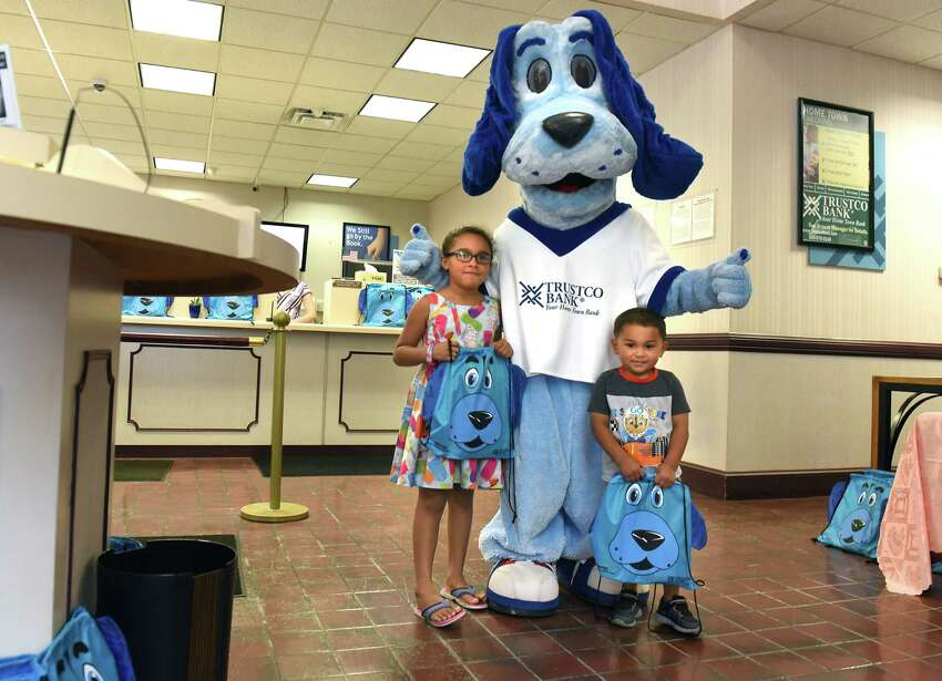 Tatiana Turner, 7, of Troy and her brother Tamren, 3, pose with their new backpacks with the mascot Trusty at Trustco Bank on Thursday, Aug. 30, 2018 in Troy, N.Y. Trustco Bank was giving away backpacks with school supplies and free lunch. (Lori Van Buren/Times Union)