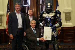 "From left, Fox Sports Southwest general manager Steve Simpson, UIL deputy director  Jamey Harrison, Cleatus the Fox Sports Robot and Texas governor Greg Abbott at the Texas State Capitol in Austin after Abbott signed a proclamation declaring Aug. 31 to Sept. 1 as ""Texas Football Days"" the Lone Star State."