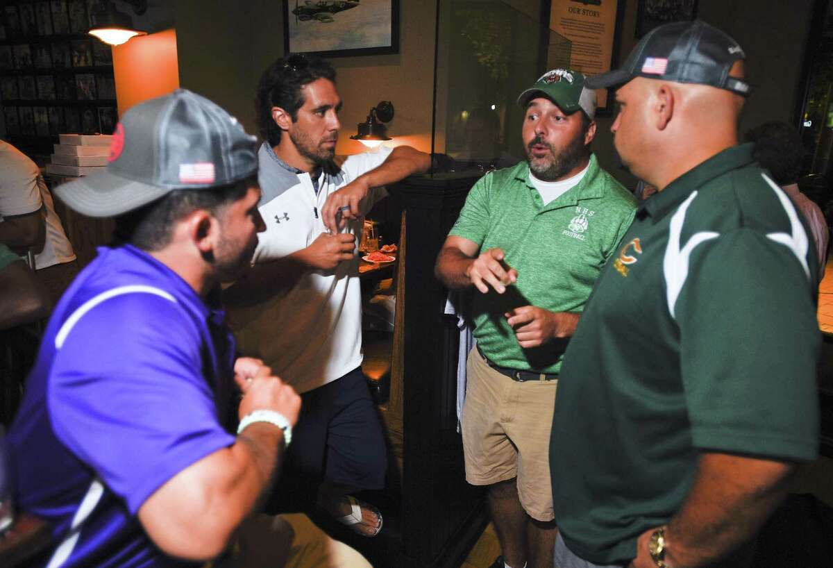Coaches, from left, Westhill's Joe Devellis, Brein McMahon Jeff Queiroga, Norwalk's Sean Ireland and Trinity Catholic Donny Panapada chat during the Ruden Report FCIAC Football Media Day at the Colony Grill on August 29, 2018 in Norwalk, Connecticut.