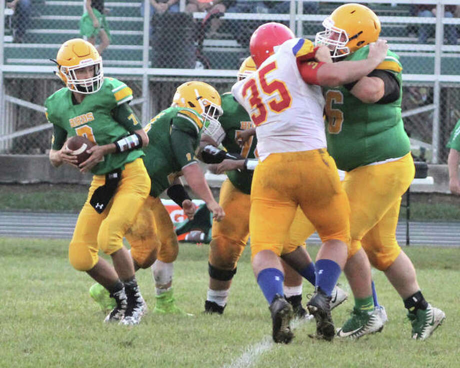 Southwestern quarterback Dylan Grizzle (left) drops back to throw while Roxana's 6-1, 240-pound pass rusher Jacob Acker (35) tries to shed the block of Piasa Birds' 6-2, 330-pound lineman Collin Albert during the Shells' Week 1 victory in Piasa. Photo: Greg Shashack / The Telegraph