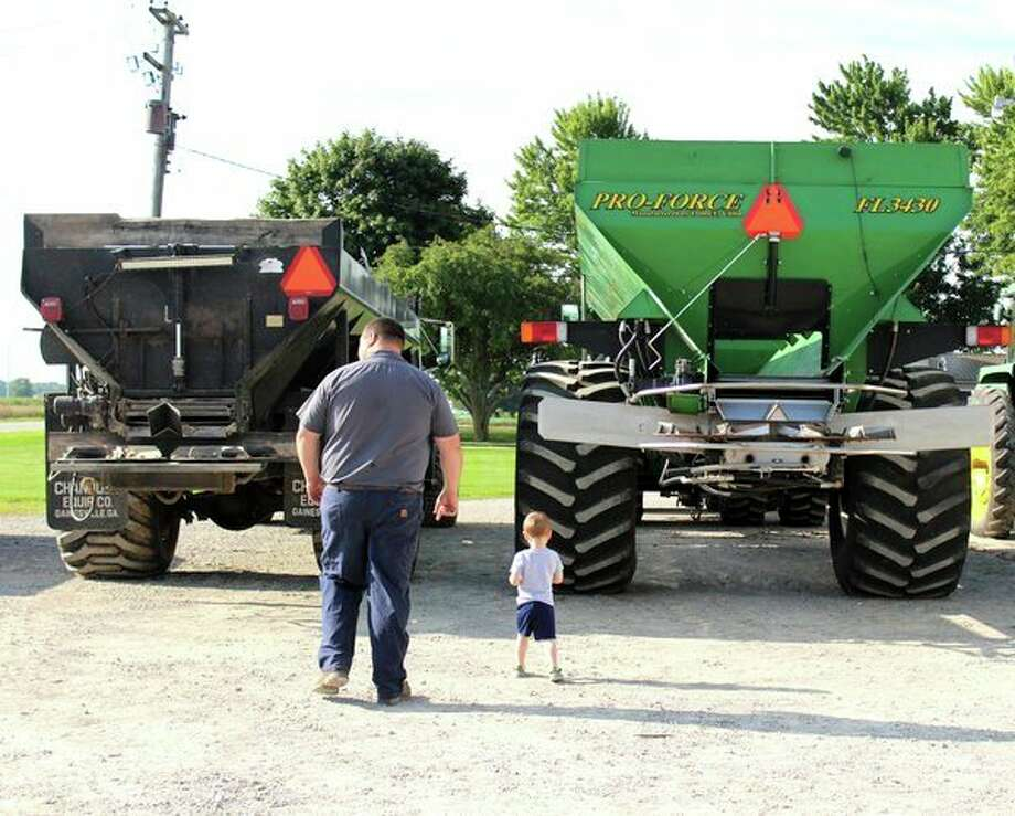 Nathan Engelhard and his son, Lawson, stand behind manure spreaders on their Unionville farm. The family recently hosted a compost demonstration for organic farmers. (Courtesy Photo)