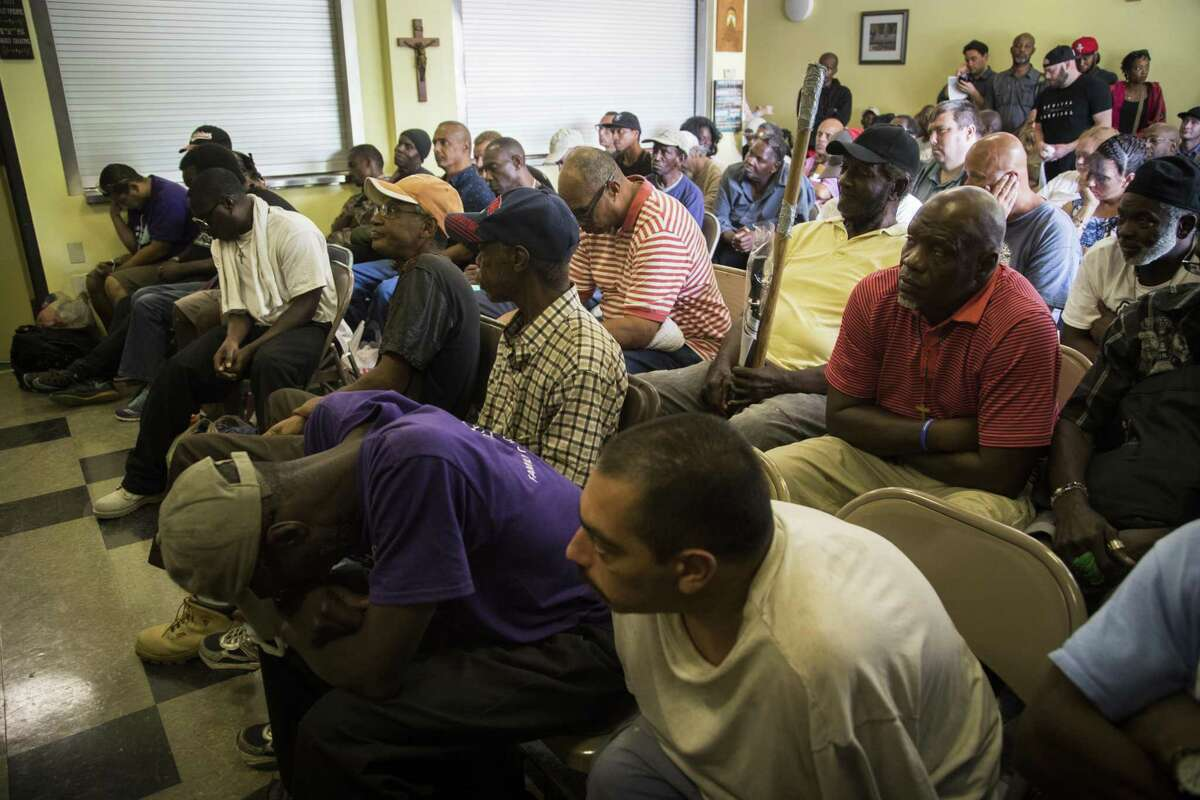 A group of homeless people gather at Lord of the Streets ministry to listen to the testimony of former Astros pitcher J.R. Richard who struggled with homelessness, Tuesday, July 17, 2018, in Houston.