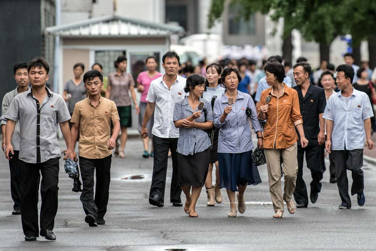 People walk along a street on August 24, 2018 in Pyongyang, North Korea. Despite ongoing international negotiations aimed at easing tensions on the Korean peninsula, the Democratic People's Republic of Korea remains the most isolated and secretive nation on earth. Since it's formation in 1948 the country has been led by the Kim dynasty, a three-generation lineage of North Korean leadership descended from the country's first leader, Kim Il-sung followed by Kim Jong-il and grandson and current leader, Kim Jong-un. Although major hostilities ceased with the signing of the Armistice in 1953, the two Koreas have remained technically at war and the demilitarised zone along the border continues to be the most fortified border in the world.