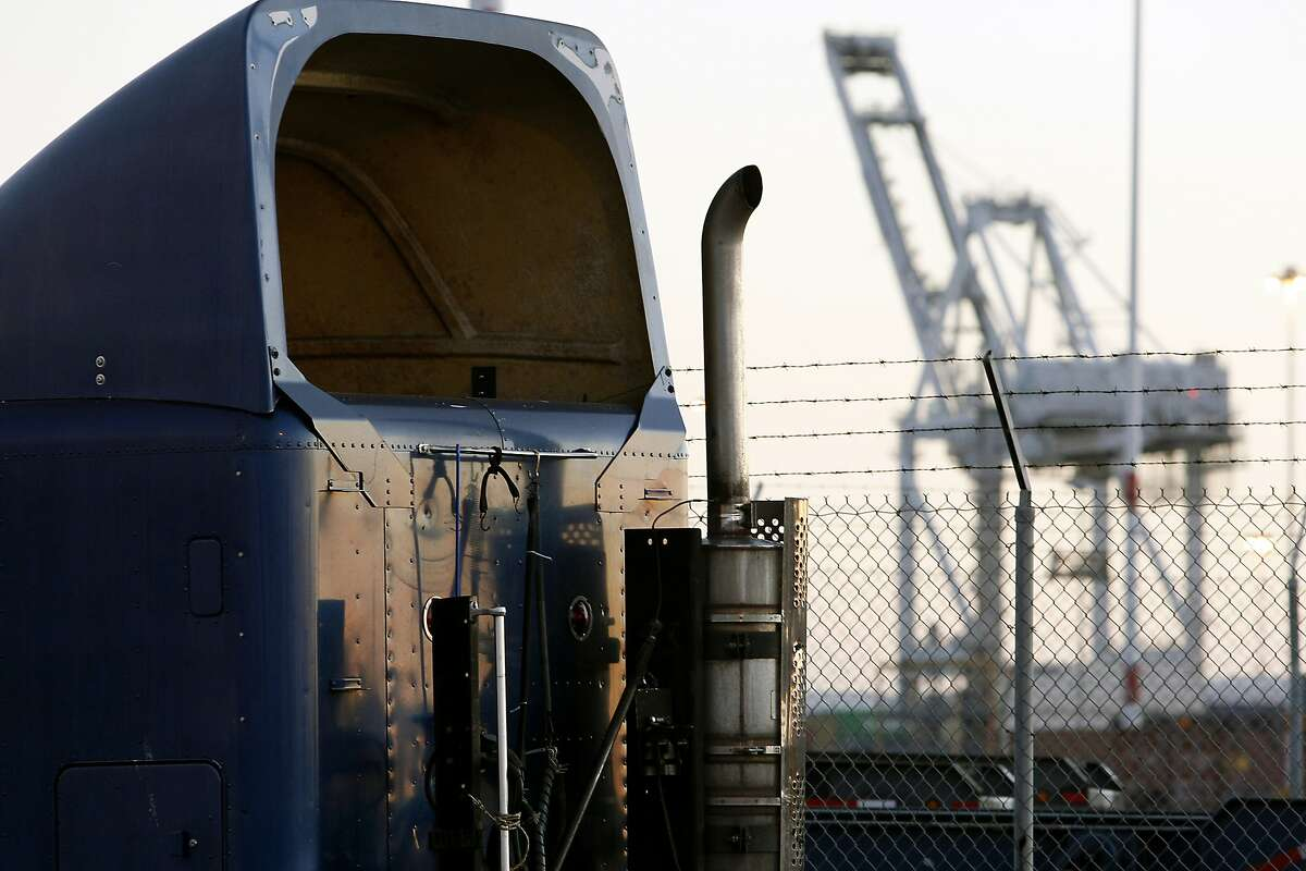 The exhaust pipe of a truck is seen with a container crane in the background at the Port of Oakland in Oakland, California Tuesday, September 17, 2013.