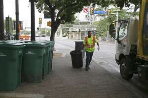 A City of San Antonio sanitation worker picks up recyclables at the corner of Losoya and East Commerce Streets on Aug. 12, 2018. Under the Alamo plan, Losoya would be widened to add a northbound lane, limiting the space available now for truck deliveries, garbage pickup and other services.