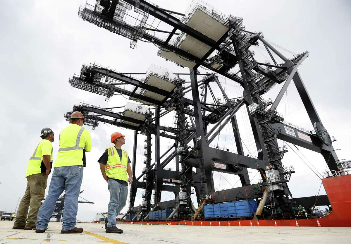 Workers pause to watch as Port Houston received it's new super post-panamax cranes, as they completed their nearly 90-day journey from Shanghai, China to the Bayport Container Terminal, in Seabrook, Tuesday, August 7, 2018.