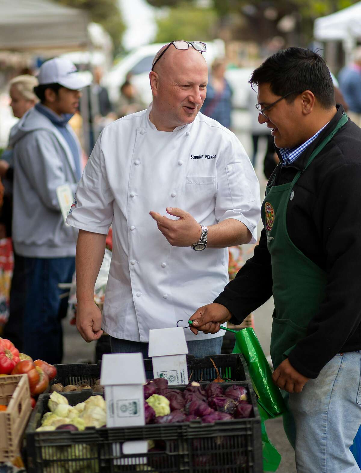Soerke Peters (left) talks with Raul Lopez of Hall's Organic Farms while shopping at the Carmel farmers' market.