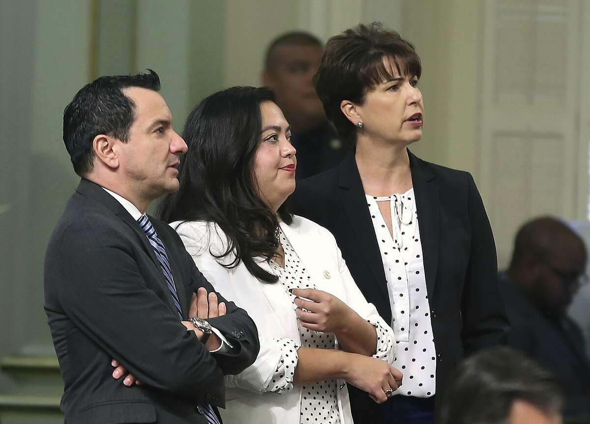 State Sen. Connie Leyva, D-Chino, right, along with Los Angeles-area Assemblywoman Wendy Carrillo, and Assembly Speaker Anthony Rendon, D-Lakewood, watches as the votes are posted for her measure to require all public universities to offer medication abortions at campus health centers, Wednesday, Aug. 29, 2018, in Sacramento, Calif. The Assembly approved the bill and sent it to the Senate. (AP Photo/Rich Pedroncelli)