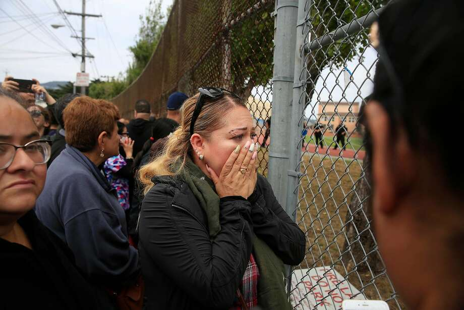 """Nelly Lizama waits outside a gate at the football field as parents wait to be reunited with their children after a gun incident at Balboa High School on Thursday, August 30,  2018 in San Francisco, Calif.  Multiple schools in the area near San Francisco's Balboa Park went into lockdown around noon Thursday after an """"incident"""" that left one student injured, three persons detained and a firearm recovered, authorities said. Photo: Lea Suzuki / The Chronicle"""