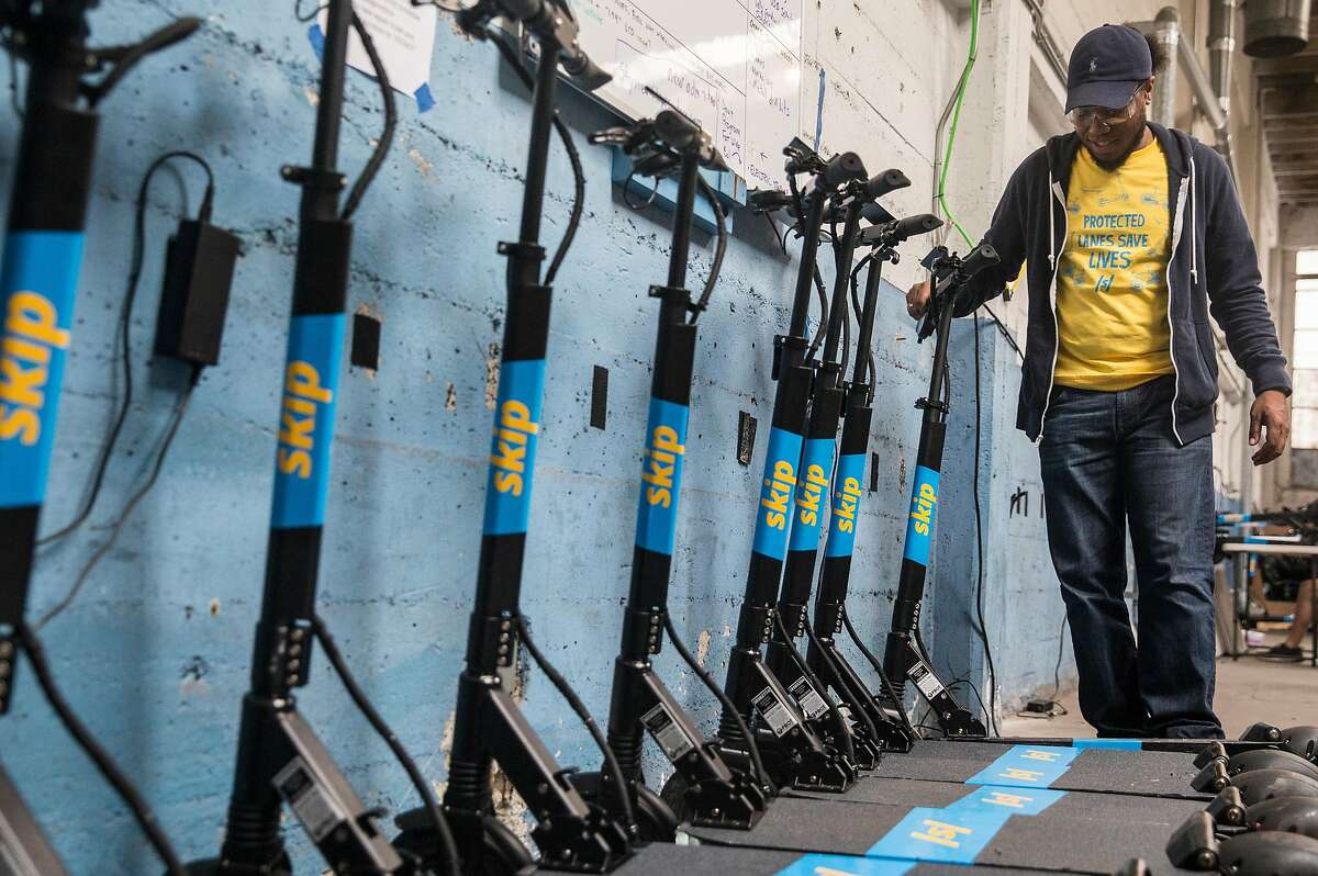 Skip technician Darcell Epps lines up a row of scooters for deployment at the main Skip warehouse in San Francisco, Calif. Thursday, Aug. 30, 2018.