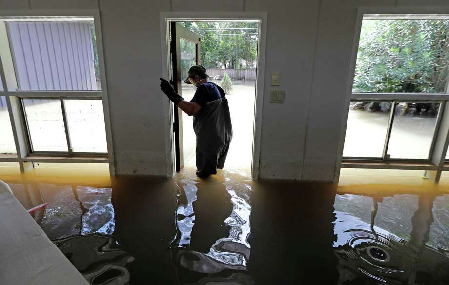 PHOTOS: Harvey's toll on neighborhoodsJuan Minutella opens the back door while helping friend collect the last of his belongings from his flooded home.