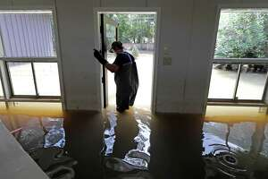 FILE - In this Sept. 4, 2017 file photo, Juan Minutella opens the back door while helping friend Gaston Kirby collect the last of his belongings from his flooded home in the aftermath of Hurricane Harvey in Houston. Houston has approved a new regulation dictating how high new homes and other structures must be elevated to avoid floodwaters. The City Council approved the rule Wednesday, April 4, 2018. It comes in the wake of Hurricane Harvey, which flooded thousands of homes in the nation's fourth-largest city. (AP Photo/David J. Phillip File)