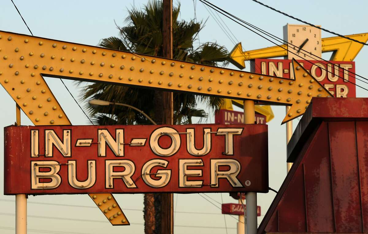In this file photo, In-N-Out Burger signs, two in the foreground from the fast food chain's original location, and one in the background at a new location across the Interstate 10 freeway, fill the skyline in Baldwin Park, Calif. rtland. (AP Photo/Adam Lau, File)
