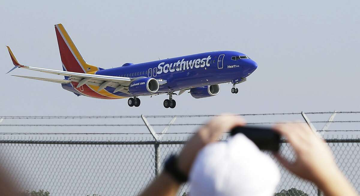 In this Sept. 8, 2014 file photo, a Southwest Airlines plane with a new paint job flies over Love Field in Dallas. On Monday, Oct. 13, 2014, Southwest will launch its first long-distance flights from its home base at Dallas Love Field to seven cities across the country, with eight more destinations next month. Such flights were prohibited until now by a longtime law that protected Dallas-Fort Worth International Airport by limiting flights from Love Field to a few nearby states. (AP Photo/LM Otero, File)