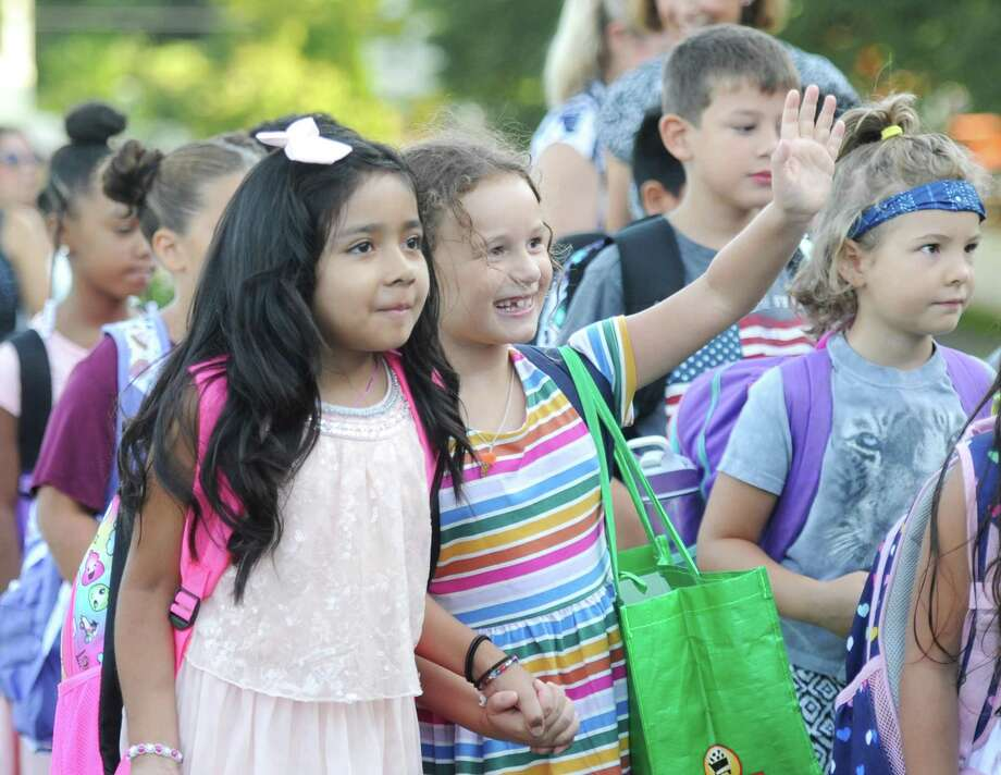 Second graders Kaylee Son, left, and Eva Csatorday march in the annual Parade of Students on the first day of school at Hamilton Avenue School in the Chickahominy section of Greenwich, Conn. Thursday, Aug. 30, 2018. As an icebreaker to welcome the kids back, students paraded with their new classmates and teachers as parents gathered to send their well wishes and take photos. Photo: Tyler Sizemore / Hearst Connecticut Media / Greenwich Time