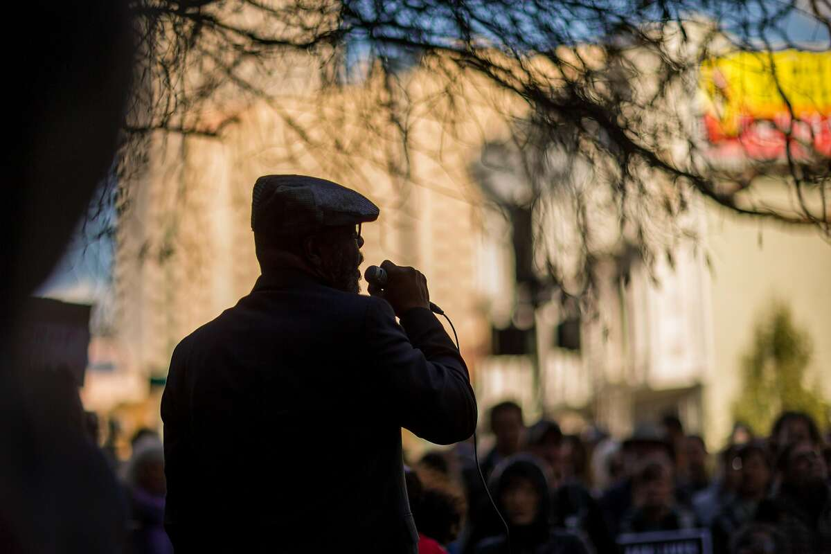 Reverend BK Woodson talks to people gathered at the Alameda County District Attorney's Office to protest the minimum wage and demand that the charges against the Black Friday 14 be dropped on Tuesday, Nov. 10, 2015 in Oakland, Calif.