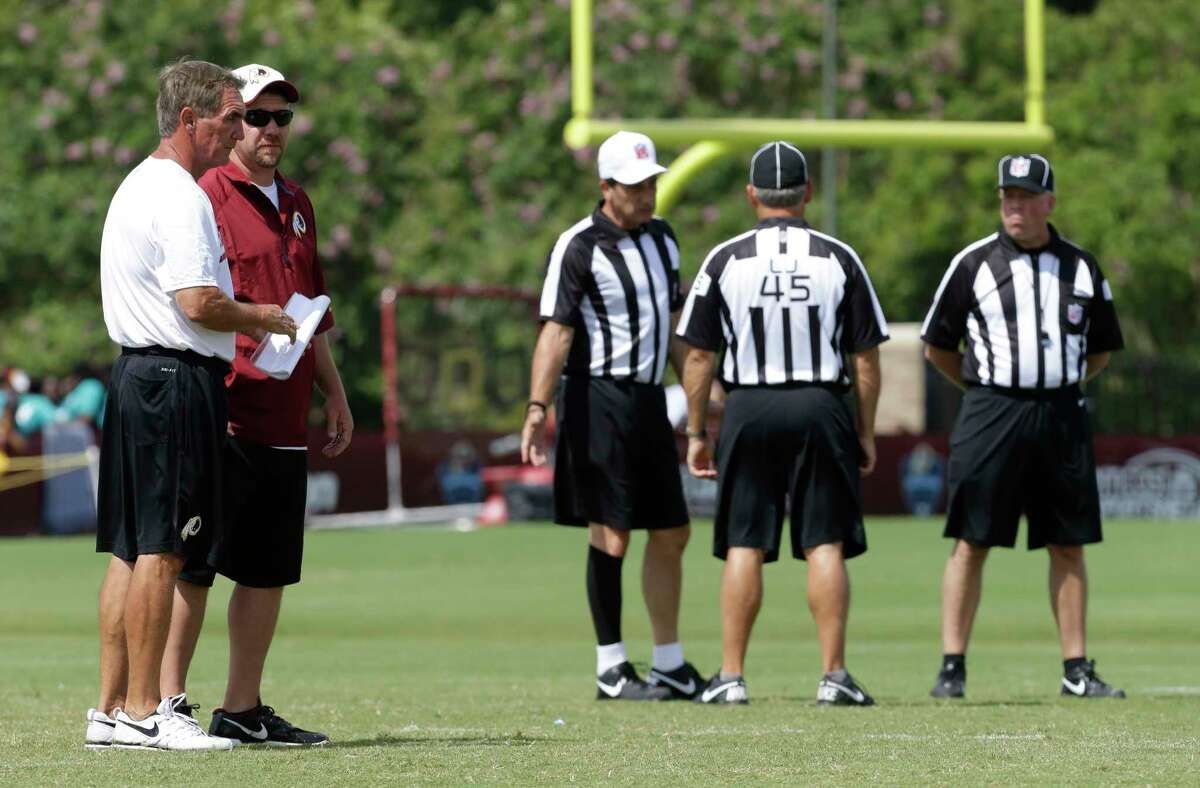 In an Aug. 1, 2013, file photo, then Washington Redskins coach Mike Shanahan talks to staff as NFL officials, including referee Gene Steratore, center,wait for practice to start at the NFL football team's training camp in Richmond, Va.. Steratore retired from officiating after the 2017 season. (AP Photo/Steve Helber) ORG XMIT: VASH103
