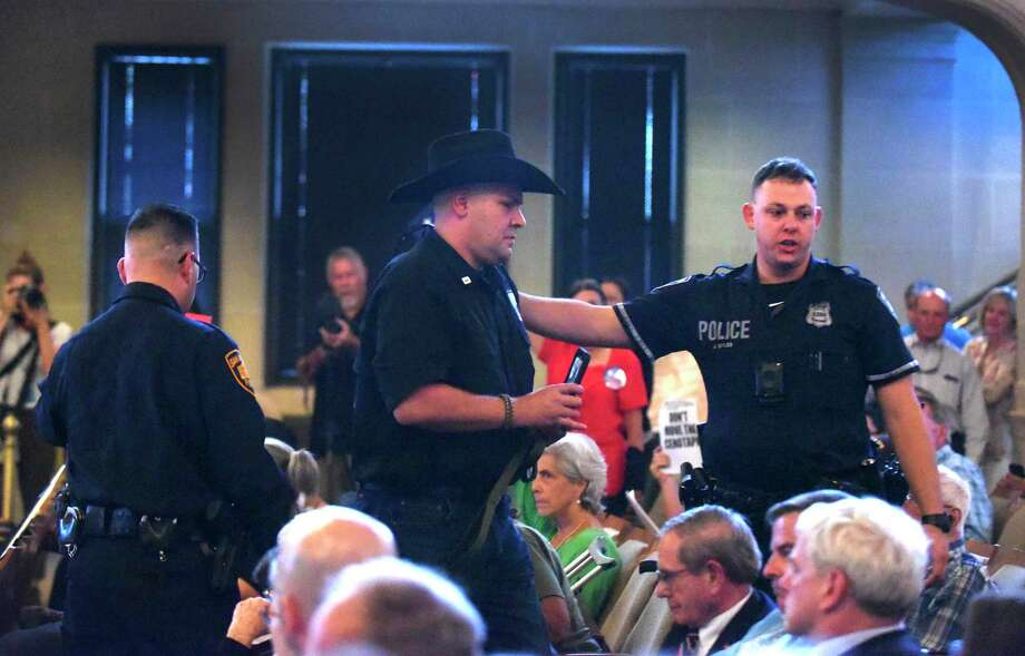 Brandon Burkhart, president of This Is Texas Freedom Force, is escorted out after an outburst during a meeting of the Alamo Citizen Advisory Committee on the proposed Alamo plan in City Council chambers on Thursday, Aug. 30, 2018. The committee approved seven resolutions supporting key concepts of the plan presented for the historic mission and battle site. Photo: Billy Calzada, Staff Photographer / San Antonio Express-News