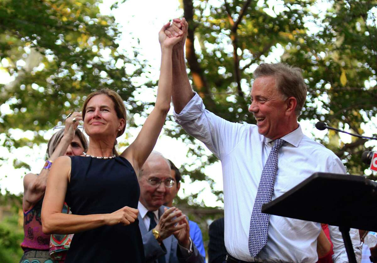 Susan Bysiewicz and Ned Lamont raise their arms after addressing the crowd gathered for a unity rally at Wooster Square Park in New Haven, Conn., on Thursday Aug. 30, 2018. During the rally, Lamont spoke about his vision for creating jobs, growing the economy and improving the business climate in Connecticut. | File photo