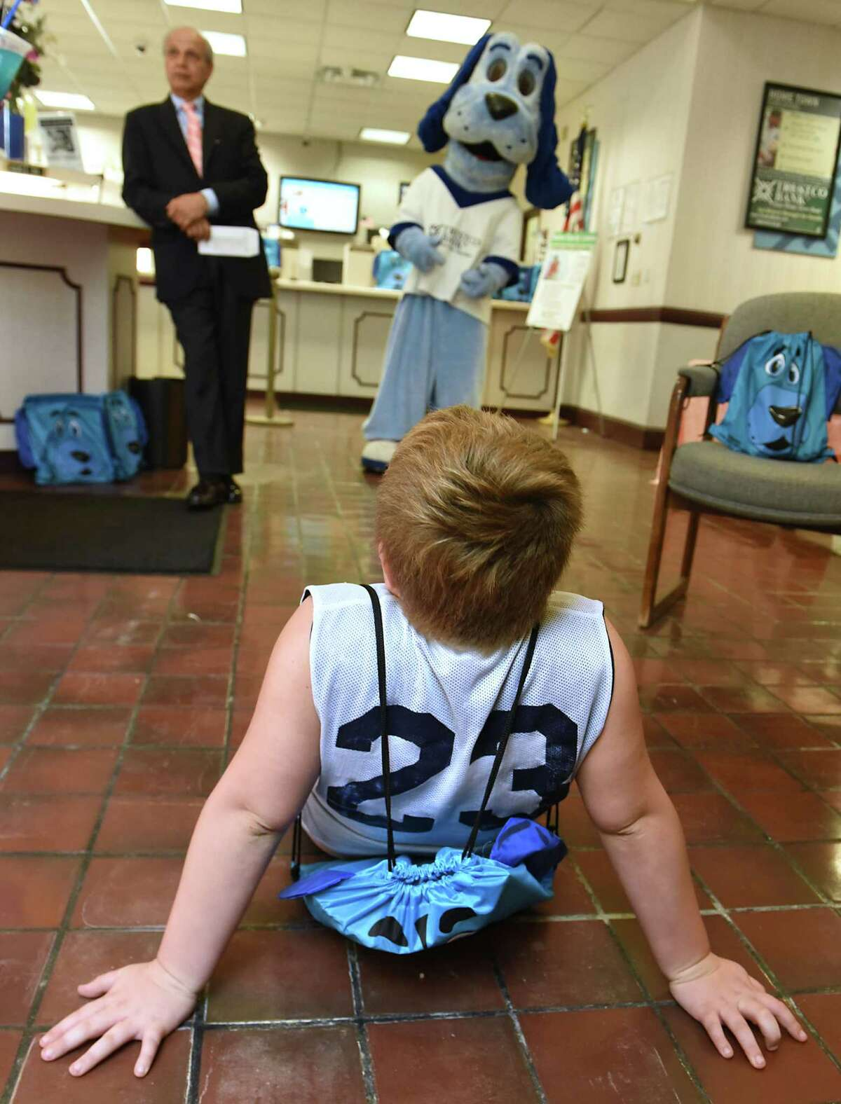 Riley Recore of Cohoes, 7, sits on the floor of Trustco Bank on a watches the mascot Trusty on Thursday, Aug. 30, 2018 in Troy, N.Y. Trustco Bank was giving away backpacks with school supplies and free lunch. Joseph Tardi, president of Joseph Tardi Associates, stands to the left. (Lori Van Buren/Times Union)