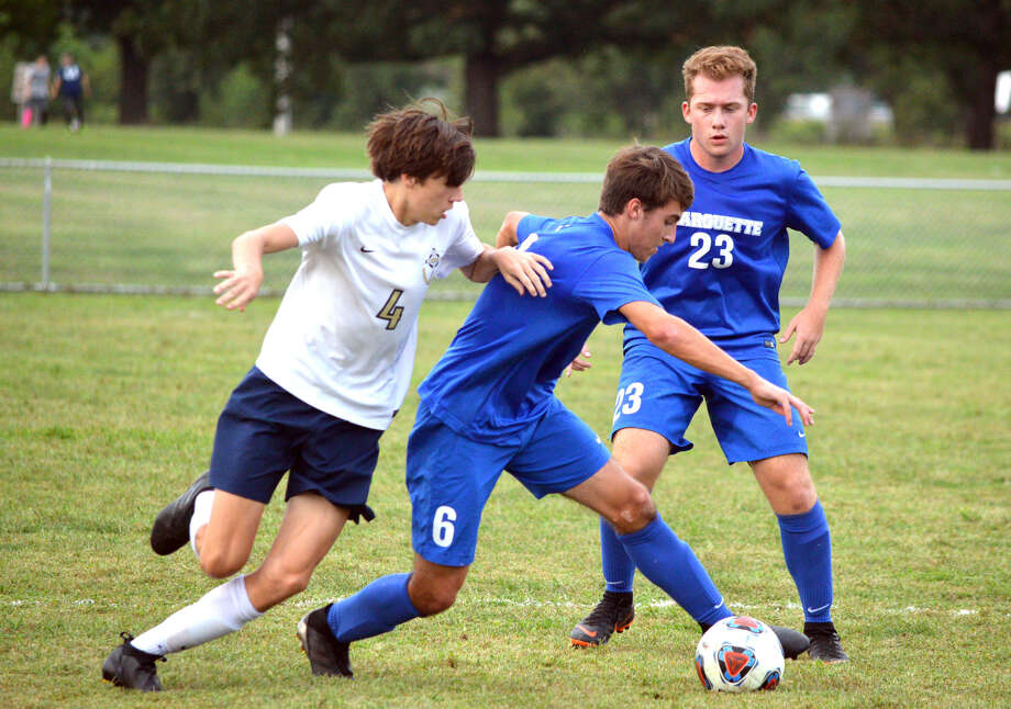 Father McGivney's Joey Crowder, left, tries to get the ball away from Marquette's Noah McClintock, middle, as Marquette's Nathan Joehl looks on during Thursday's game an Gordon Moore Park. Photo: Scott Marion