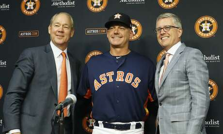 Astros manager A.J. Hinch, sandwiched between owner Jim Crane and general manager Jeff Luhnow, is all smiles during a Thursday news conference at Minute Maid Park announcing a contract extension through 2022 for the skipper.