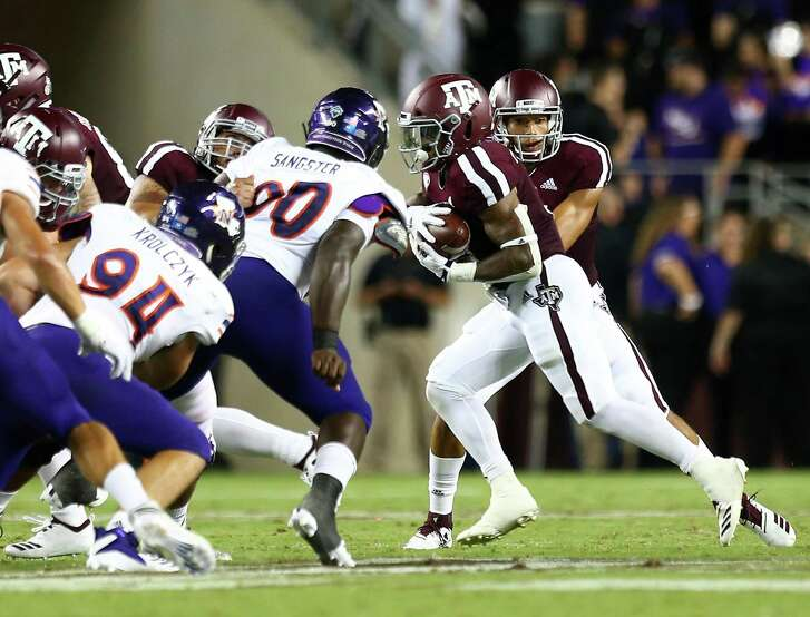 A&M quarterback Kellen Mond (11) hands the ball off to running back Trayveon Williams (5) during the first quarter of the game against Northwestern State at Kyle Field on Thursday.