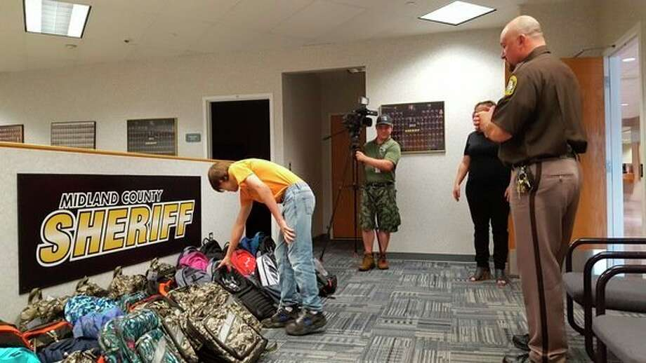 A foster teenslooks over new backpacks full of school supplies Monday at the Midland County Sheriff's Office.