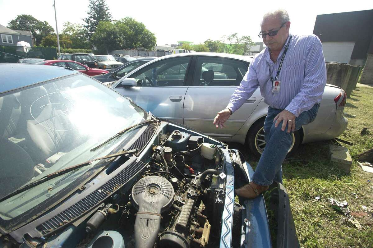Fleet Manager Michael Scacco points to the engine of a car sitting in the city's fleet management lot on Magee Ave. after being abandoned and towed in Stamford, Conn. on Tuesday, Aug. 28, 2018. The car was left in this stripped condition before being towed to the lot and will soon be auctioned off for parts.
