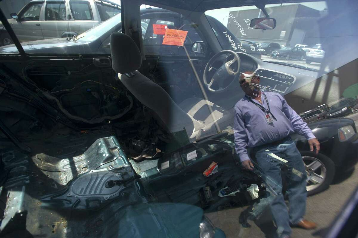 The reflection of fleet manager Michael Scacco is seen in the window of a stripped car sitting in the city's fleet management lot on Magee Ave. after being abandoned and towed in Stamford, Conn. on Tuesday, Aug. 28, 2018. The interior of the car, including the passenger seat and entire back row, has been entirely stripped and was towed after being abandoned on a city street.