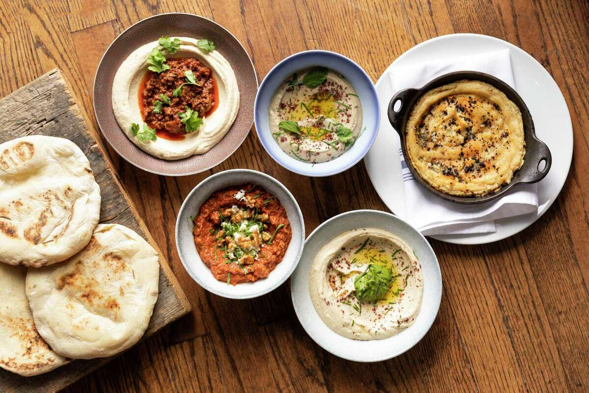 Top, from left: Hummus with ground lamb; Mutabal (eggplant dip); Turkish hummus. Bottom, from left: Muhamara (roasted red pepper and walnut spread); hummus with green tehina at One Fifth Mediterranean