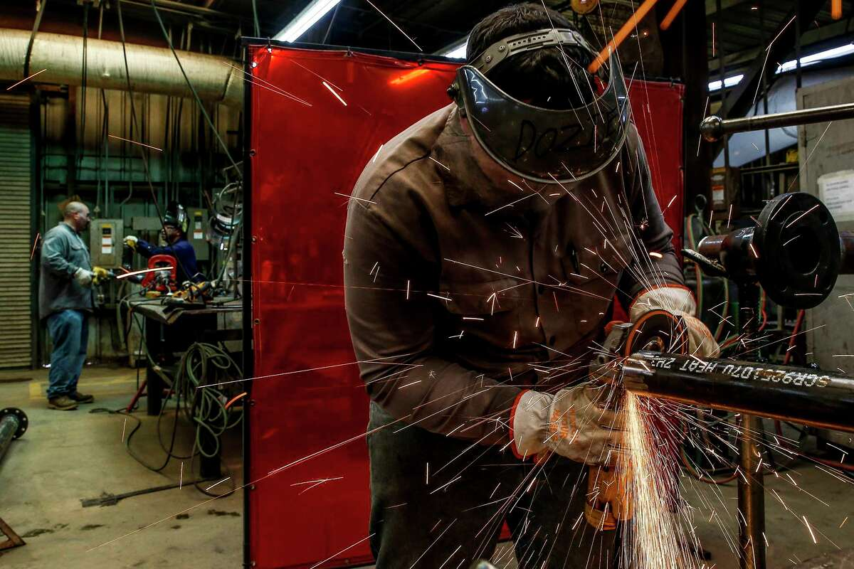 Zachary Construction pipe fitter Phillip Dozier grinds down a piece of pipe at the contractor's fabrication site at BASF's petrochemical facility Thursday Aug. 30, 2018 in Freeport.