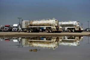 Trucks are seen reflected in a puddle at Love's Travel Stop in Pecos, Texas, U.S., on Wednesday, July 18, 2018. Thousands of workers now reside in dormitory-like compounds, referred to as 'man camps,' in the Permian Basin, a more than 75,000-square-mile expanse of sedimentary rock that's one of the world's biggest oil plays, drawing billions of dollars in new investment. Photographer: Callaghan O'Hare/Bloomberg