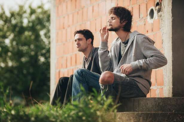 Depressed and sad young man smoking cannabis or hashish joint with his friend