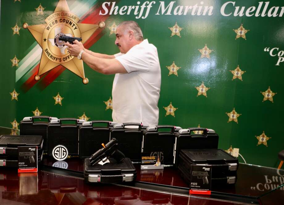 Webb County Sheriff Martin Cuellar demonstrates one of the 12 handguns provided by a National Rifle Association grant. Photo: Courtesy Photo