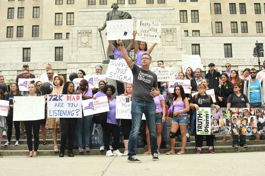 Keith Brown, director of health and harm reduction at the Katal Center for Health, Equity and Justice, center, speaks as people gather in West Capitol Park to observe International Overdose Awareness Day (IOAD) by remembering those lost to overdose, and demand action to prevent future deaths on Friday, Aug. 31, 2018 in Albany, N.Y. (Lori Van Buren/Times Union) Photo: Lori Van Buren, Albany Times Union / 20044639A