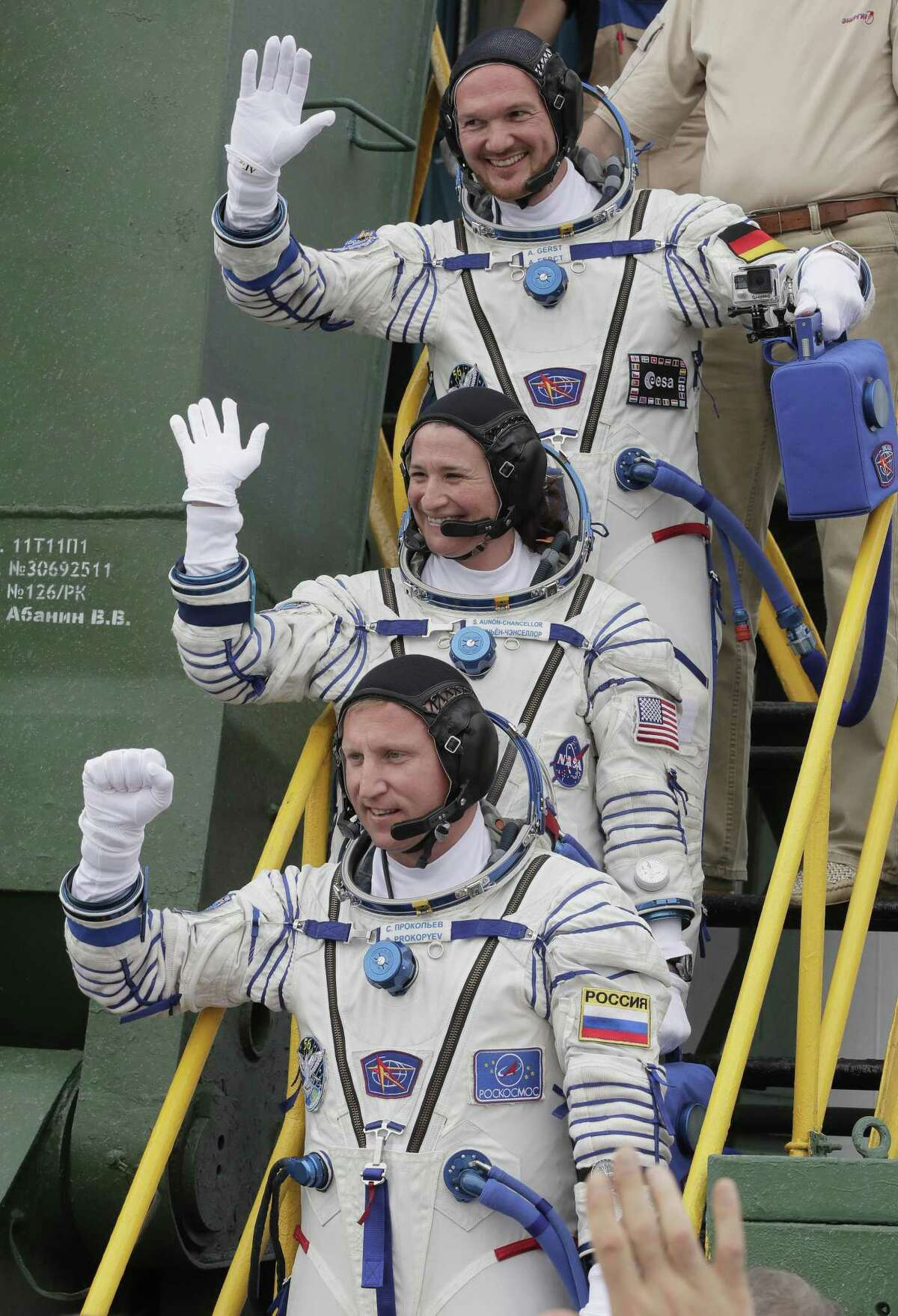 U.S. astronaut Serena Aunon-Chancellor, center, Russian cosmonaut Sergey Prokopyev and German astronaut Alexander Gerst, top, wave as they board prior to their June 2018 launch to the International Space Station. Astronauts scrambled Thursday, Aug. 30 to patch a tiny hole in a Russian capsule that was allowing air to leak from the space station.