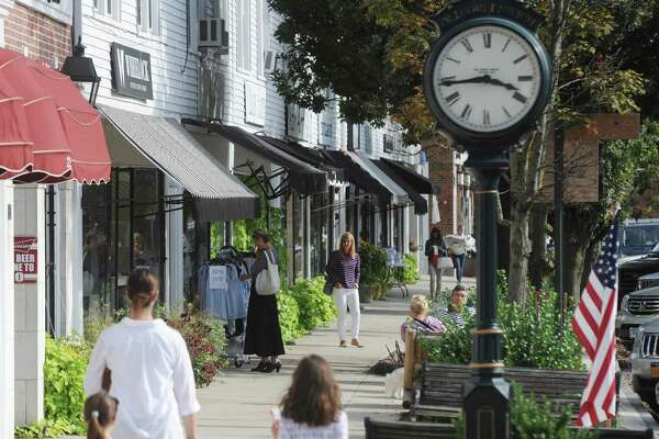 Shoppers walk down the Sound Beach Avenue business district in Old Greenwich, Conn. Tuesday, Sept. 27, 2016.