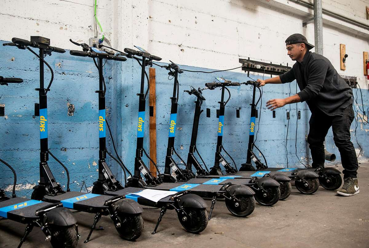 Skip technician Daniel Gutierrez lines up a row of scooters for deployment at the main Skip warehouse in San Francisco. After a temporary ban, scooters are about to hit the streets of San Francisco again.