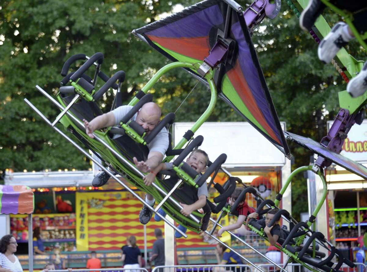 Peter Bridgers of Stamford and his son Benjamin, 7, fly on Cliff Hanger as they take in the 38th Annual St. Leo's Fair on August 30, 2018 in Stamford, Connecticut. The fair, offering family fun, amusement rides, good eating, live music, bingo and a $35,000 prize raffle, ends Saturday, opening at 2:00pm to 11:00PM.