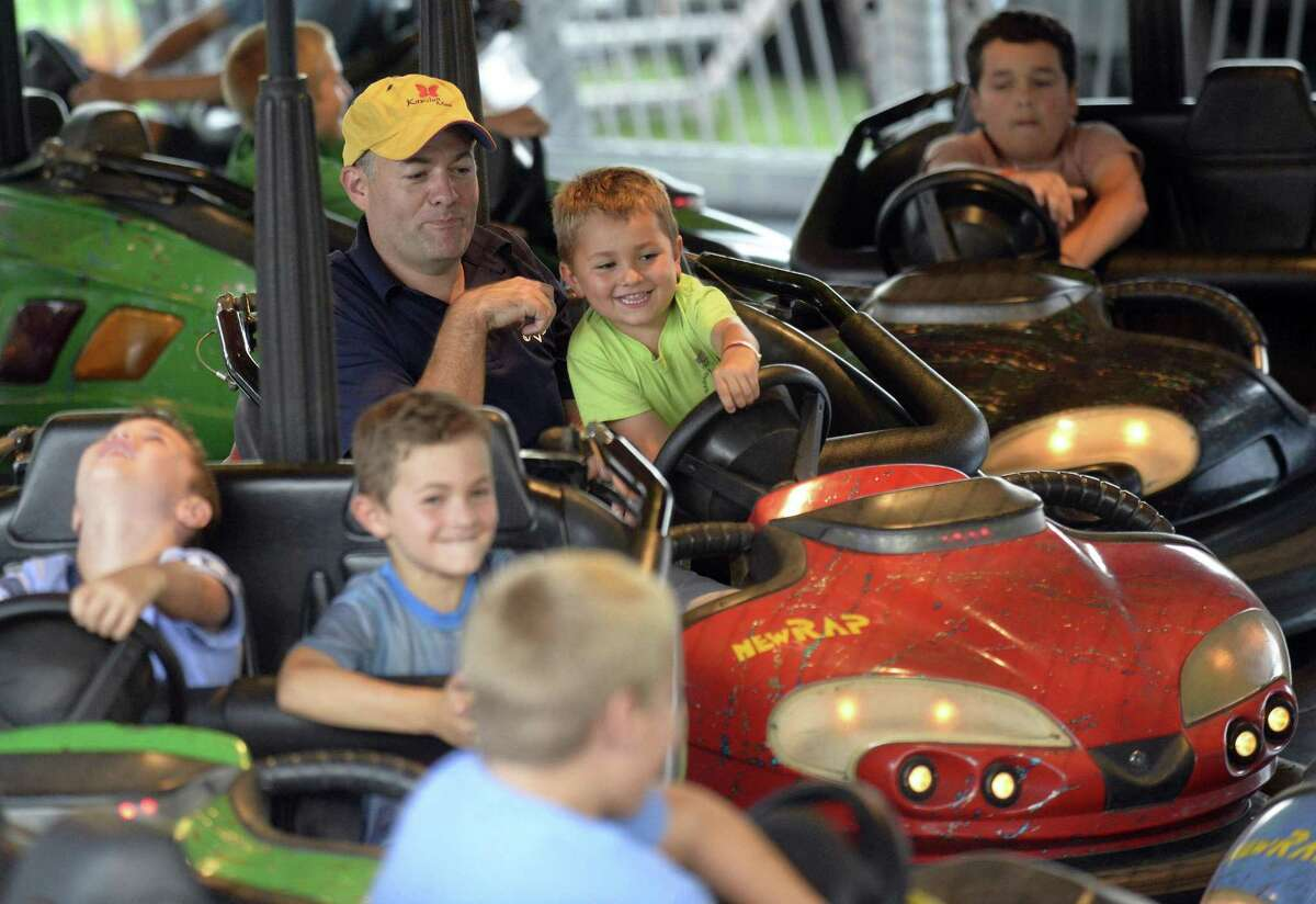 Jeff Black of Stamford and his son Declan enjoy bumping friends as they ride the bumper cars and take in the 38th Annual St. Leo's Fair on August 30, 2018 in Stamford, Connecticut. The fair, offering family fun, amusement rides, good eating, live music, bingo and a $35,000 prize raffle, ends Saturday, opening at 2:00pm to 11:00PM.